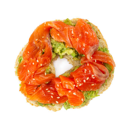 Sliced salmon with avocado on bagel with sesame seeds isolated on white background. Top view. Zdjęcie Seryjne