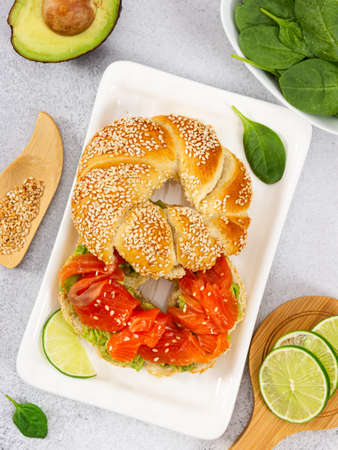 Sliced salmon with avocado on bagel with sesame seeds on gray stone background. Top view. Perfect healthy breakfast.