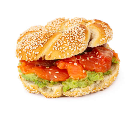 Sliced salmon with avocado on bagel with sesame seeds isolated on white background. Perfect healthy breakfast.