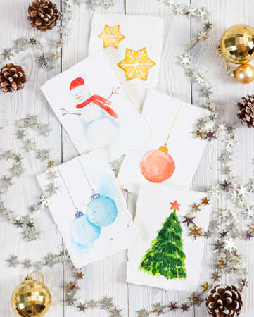 Workplace of the artist with christmas pictures on light wooden background. Christmas concept.