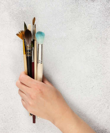 Artistic brushes in a female hand on a gray stone background.