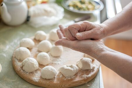 Home cooking. A woman's hands while sculpting pies. Balls from the dough on a wooden board.