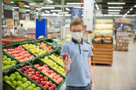 A teenager in a supermarket holding an apple. Hes wearing a mask and gloves.