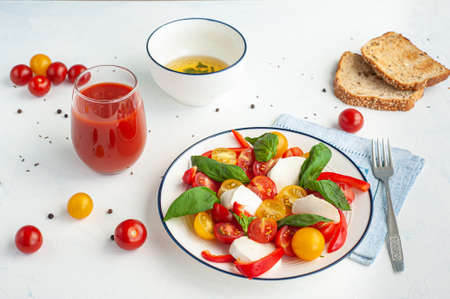 Salad with tomatoes, peppers, mozzarella. Tomato juice and toast.