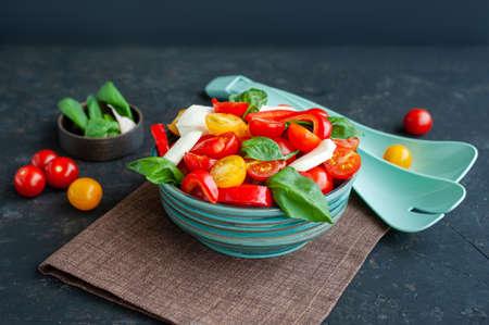 Summer tomato, mozzarella and basil salad in a bowl against a dark background. Archivio Fotografico