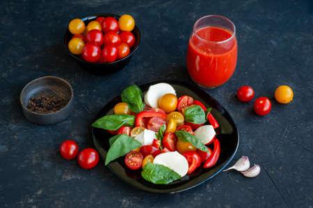 Summer salad on a dark background in a black plate. Tomato juice in a glass. Spices. Tomato salad, basil and mozzarella. Archivio Fotografico