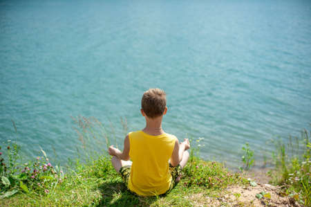 The boy is sitting on the shore. The boy does yoga. The boy is tanning. Reklamní fotografie