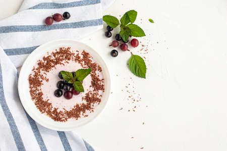 Yogurt with chocolate and currant berries and gooseberry decorated with mint on a white background with a napkin in a strip. Copy spase. Top view. 版權商用圖片
