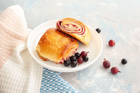 Fresh buns with berry filling decorated with black currants and gooseberry on a light blue concrete background.