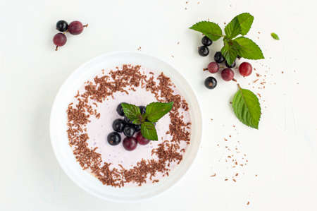 Yogurt with berry jam decorated with currants, gooseberry and mint. View from above.