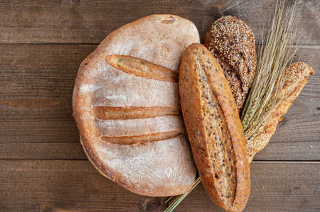 The bakery, several different fresh loaves of bread with a crisp crust, sprinkled with seeds and sesame seeds on a wooden background with ears of wheat.