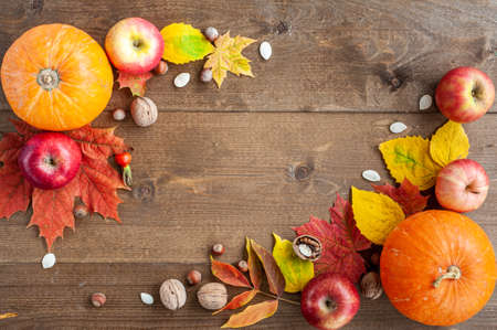 Thanksgiving. Harvest. The composition of autumn fruits, vegetables, nuts and leaves on a brown wooden background. View from above. A place for text. Standard-Bild