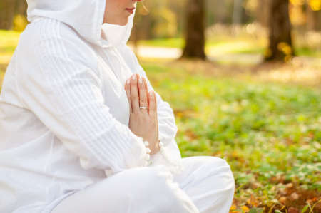 A girl plus a size in a white suit with a hood doing yoga and meditating in the park. Yoga and wellness concept Hands close up Copy space