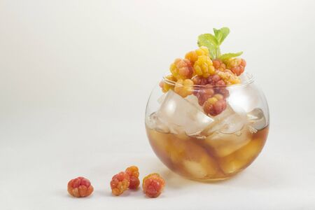 Cocktail with cloudberry, ice and tea in a glass.