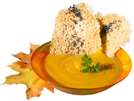 Plate with Pumpkin soup, cheese chips and autumn maple leaves. Isolated on white.