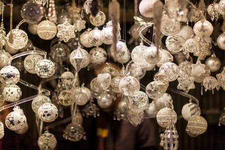 White and silver Christmas tree ornaments and balls, advent market stall close up photo Stock Photo