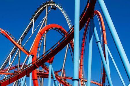 Rails de montagnes russes colorés rouges et bleus, construction de divertissement, journée d'été ensoleillée au parc d'attractions