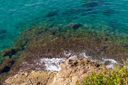 Clear blue water, sea waves running on the rock shore, sunny summer day by the ocean Stok Fotoğraf