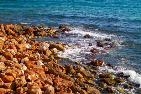 Clear blue water, sea waves running on the red rock shore, sunny summer day by the ocean