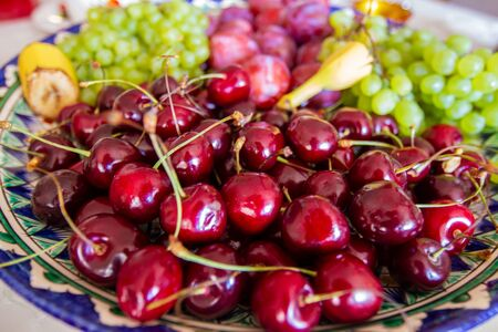 Delicious vibrant colored fresh fruits and berries variety on an asian patterned plate: sweet cherries, bananas, graped, plums, healthy vegan food close up