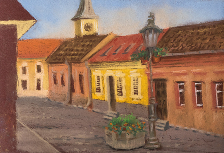 Traditional European urban landscape. Old European street with ancient houses, tiled roofs, church and street lights.