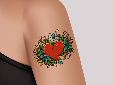 Tattoo on shoulder. Heart decorated with flowers