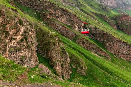 Ropeway in Caucasus Mountains. Red cable car moves down iron cable. Beautiful mountain landscape of Caucasus.