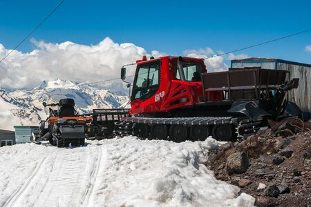 Red snowcat transport on white snow cleans ski track near mountain shelter. Caucasus Mountain