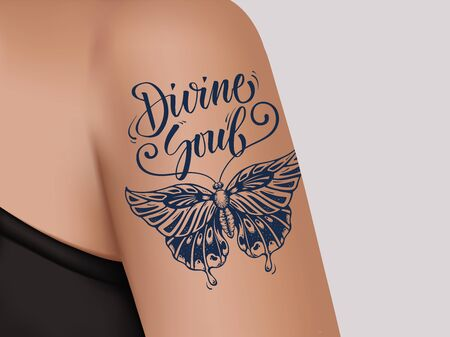 Tattoo on female shoulder. Mystic butterfly tattoo with lettering Divine Soul.