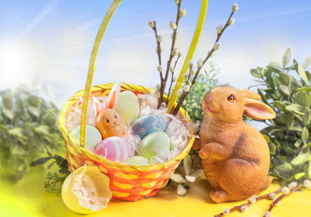 Easter decoration. Easter basket with flowers, eggs and cute Easter bunny on a pastel pink background.
