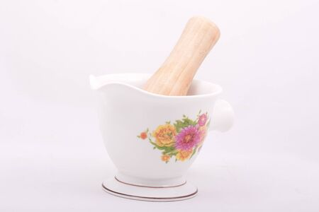 white mortar for crushing, for cooking, a wooden pestle, ceramic mortar Stock Photo
