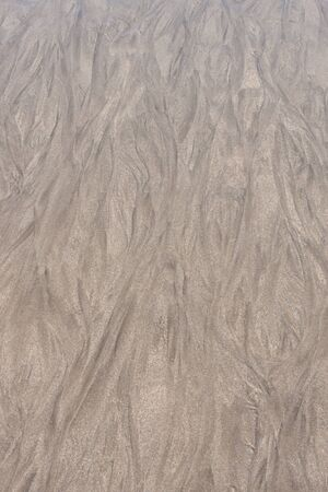 texture or background sand after the waves brush