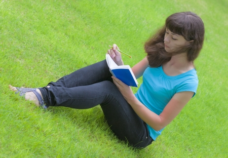 attentiveness: woman writing letter on the green lawn