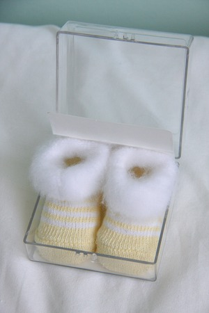 bootees: two soft beige newborn shoes baby bootees Stock Photo