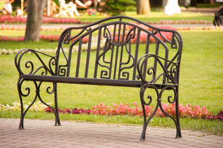 bench in the park with grass and flowers