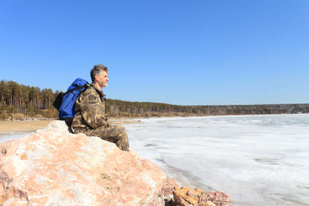 held down: The man with bicycle costs on stones at the river which has been held down by ice