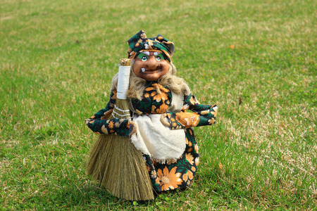 hag: The toy the old kind hag with a sweeper is on a green grass