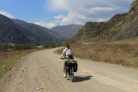 The woman goes by bicycle on the road among mountains photo