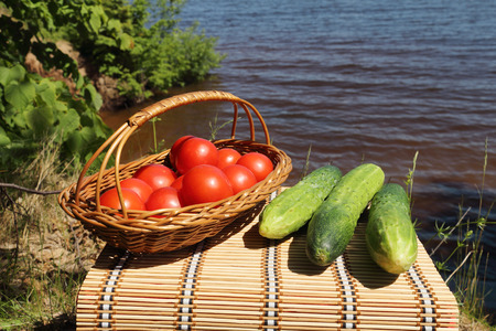 little table: Vegetables and on a little table are in a basket on the river bank Stock Photo