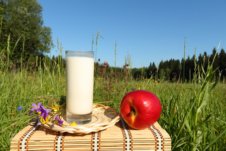 little table: The glass with milk and apple is on a little table outdoors Stock Photo