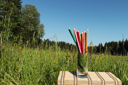 little table: Color pencils in a glass is on a little table outdoors