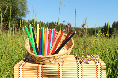 little table: Color pencils in a basket is on a little table outdoors Stock Photo