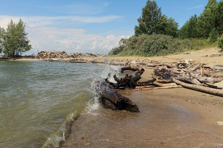 sputter: Wave splash among logs on the river bank Stock Photo