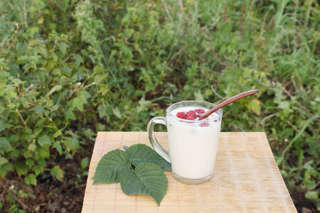 little table: The glass mug with milk and a wooden spoon with raspberry is on a little table outdoors Stock Photo