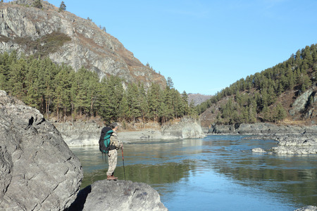 The traveler with a backpack standing  on a stone on the river bank among mountains photo