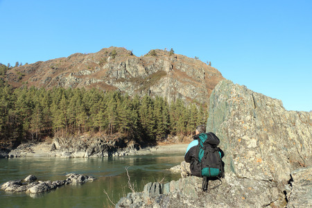 upper half: The traveler with a backpack sitting on a stone on the river bank among mountains Stock Photo
