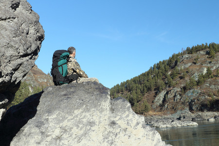 The traveler with a backpack sitting on a stone on the river bank among mountains photo