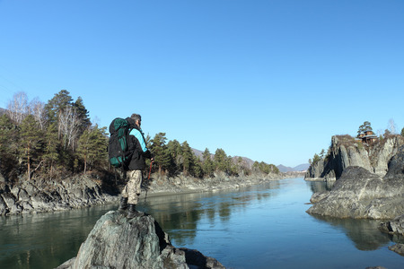 The traveler with a backpack standing on a stone on the river bank among mountains looking at the temple which is on the rocky island Patmos in Altai photo