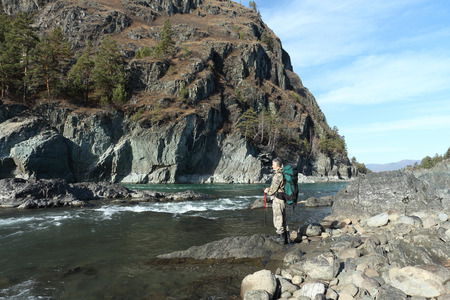 The traveler with a backpack and tracking sticks standing on a stone on the river bank among mountains photo