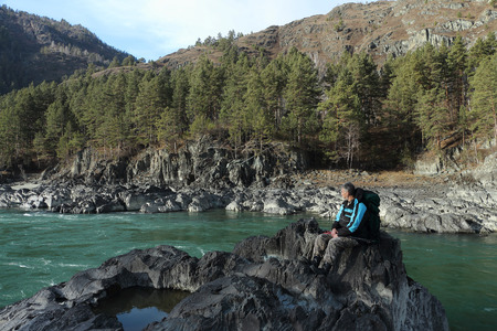 The traveler with a backpack and tracking sticks sitting on a stone on the river bank among mountains photo